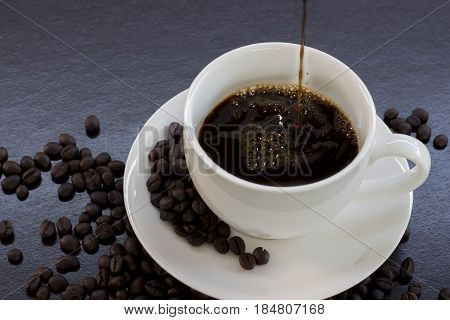 Pour black coffee into a white cup and coffee beans on a black table.