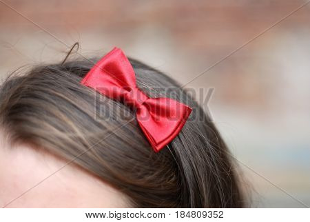 girl with red bow tie in hair