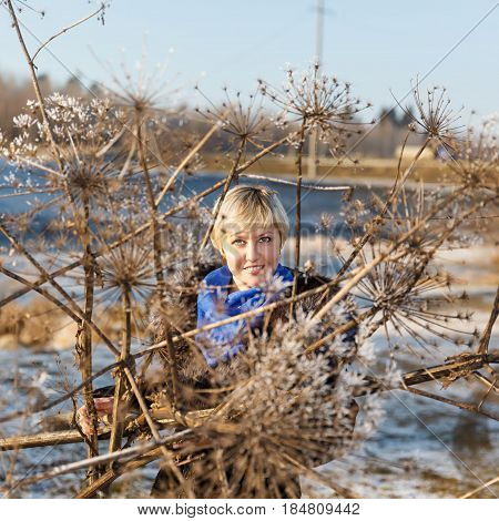 Winter landscape, girl with blond hair in a black fur coat and dry plant covered ice and snow on a background river under the ice and tree branches covered with white frost