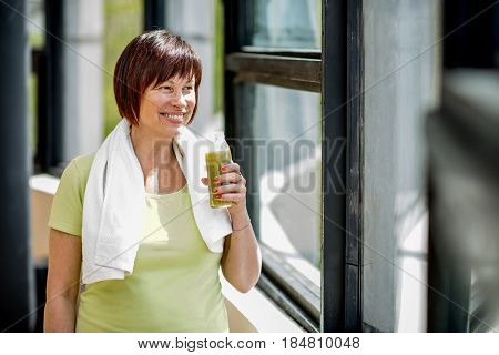Older woman drinking smoothie after the training indoors near the window