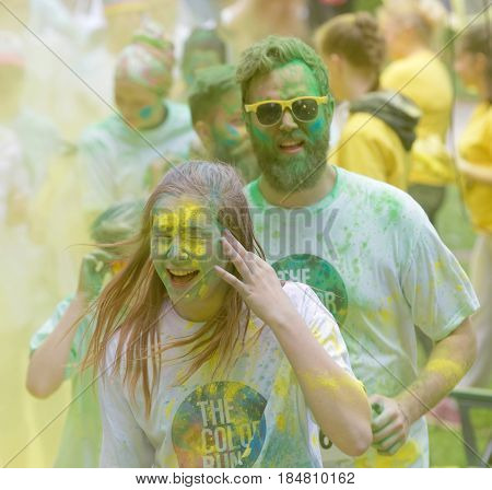 STOCKHOLM SWEDEN - MAY 22 2016: Smiling woman and men covered with yellow and green color dust in their face in the Color Run Event in Sweden May 22 2016