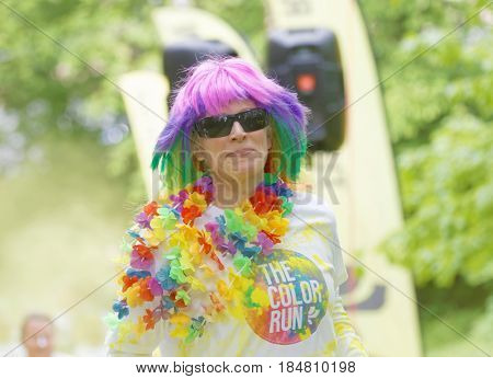 STOCKHOLM SWEDEN - MAY 22 2016: Smiling senior woman with colorful wig and a colorful flower neckless in the Color Run Event in Sweden May 22 2016