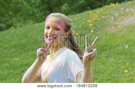 STOCKHOLM SWEDEN - MAY 22 2016: Happy young woman with silver color dust in her face making victory sign in the Color Run Event in Sweden May 22 2016