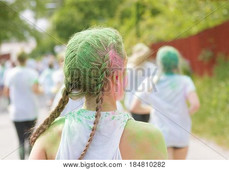 STOCKHOLM SWEDEN - MAY 22 2016: Rear view of young woman with green color dust in her hair in the Color Run Event in Sweden May 22 2016