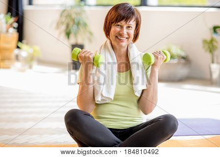 Portrait of an older woman in sportswear exercising with dumbbells indoors at home or gym