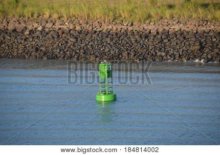 Green buoy in shipping lane passageway through canal