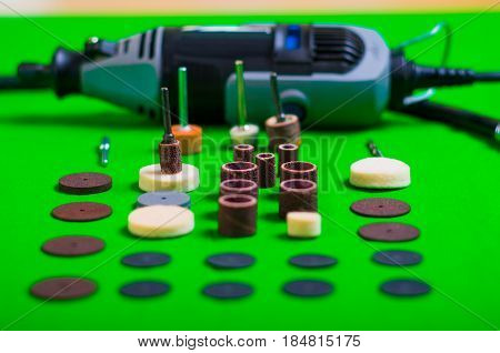 A gray drill behind of the drilling accessories on green background.