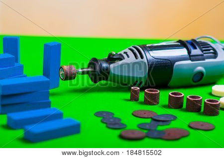A gray drill with some drilling accessories with a small blue wooden pieces on a green background.