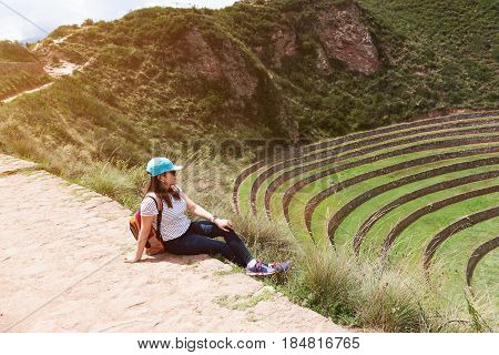 Traveller woman in Inca moray ruins terraces. Tourist woman sit in Peru old inca ruins valley