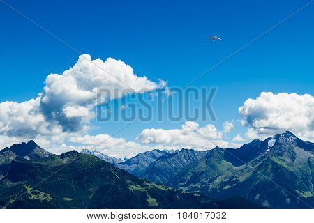 High mountains landscape with hang glider in soaring flight. Austria Tirol Zillertal