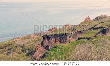 Deep Sandy Cliff On The Background Of Blue Sky. The Destruction Of The Coast As A Consequence Of Soi