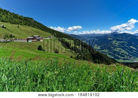 Low angle view of green meadow and alpine village with high mountains under blue sky. Austria Tirol Zillertal Zillertal High Alpine Road