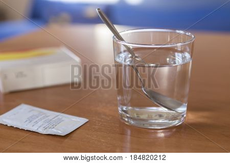 Glass of water with spoon inside to take medicine soluble on wooden table