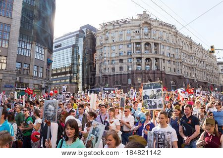 Moscow, Russia - May 9, 2016: Immortal Regiment procession in Victory Day - thousands of people marching along Tverskaya Street toward the Red Square with flags and portraits in commemoration of their loved ones who fought in World War Two