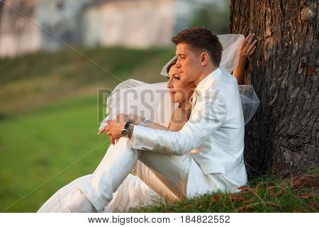 Bride's Veil Blows Up While She Sits With A Groom On The Grass