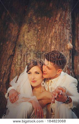 Sunset Illuminates Newlyweds Faces While They Sit Beneath The Tree