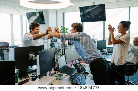 Business team cheering at good news as they congratulate each other on a success. Colleagues high fiving and clapping celebrating success.