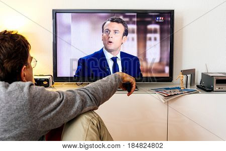 PARIS FRANCE - MAY 03 2017: Supporter of President watch the TV debate between Emmanuel Macron and Marine Le Pen on a home TV screen on May 03 2017 in Paris France. France will hold the second round on May 07 2017