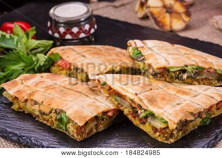 Spicy flat cake with forcemeat from salty vegetables with greens and spices