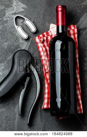 Bottle of red wine and corkscrew on black slate background