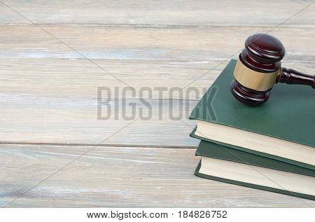 Books and wooden judge gavel on wooden background. Copy space for text. Law concept