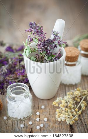 Mortar Of Dried Healing Herbs And Bottles Of Homeopathic Globules.  Homeopathy Medicine Concept.