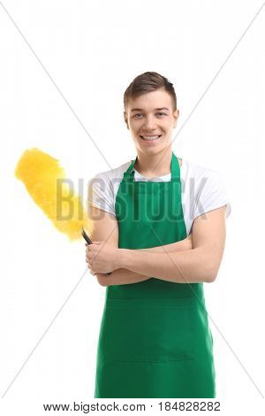 Cleaning concept. Young man in green apron with duster on white background