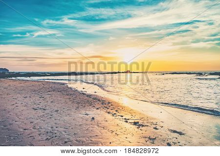Coast of the sea at colorful sunset, Nang Thong Beach, Andaman Sea, Khao Lak, Thailand. Beach sunset is a golden sunset sky with a wave rolling to shore as the sun sets over the ocean horizon.