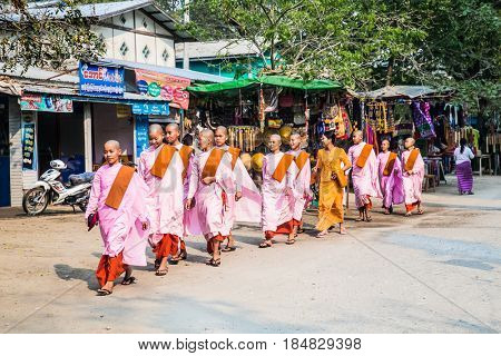 MINGUN, MYANMAR, MARCH 6, 2017: Buddhist nuns are walking at the streets of Mingun on March 6, 2017 in Myanmar. (Burma)