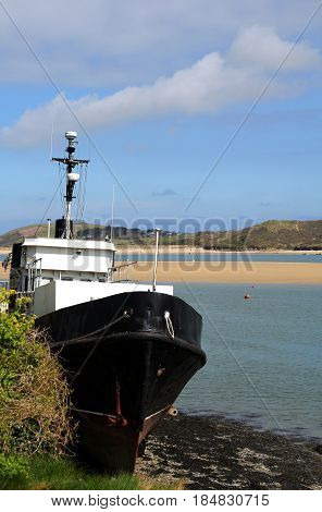 Black and white trawler boat aground at low tide in a sandy estuary