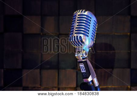 MINSK BELARUS - SEPTEMBER 29 2015: Silver old fashioned stage microphone- SHURE Super 55 Deluxe against wood background. Room for sound recording concept.