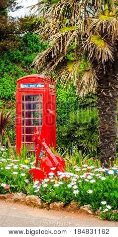 Red telephone booth and red solid anchor green vegetation background exotic trees and palm trees seaside resort sunny day