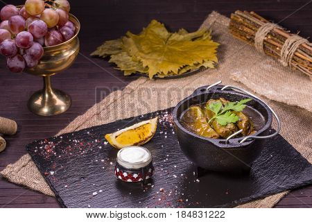 Marinated grape leaves with stuffing of mutton and rice, are served with a lemon and sour cream
