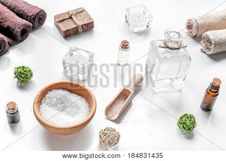 spa cosmetics set with soap, salt, oil, towels, candles on white desk background