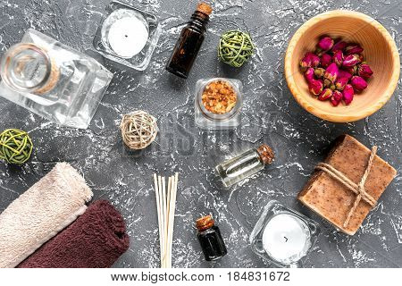 spa set with towels and organic soap on dark table background top view