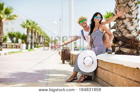 Young couple smiling on the sea coast. Summer vacation
