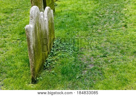 Headstones on an old small grassy cemetery.