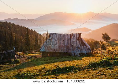 Shepherd house in high mountain. Orange sunrice glowing by sunlight. Summer time in highland