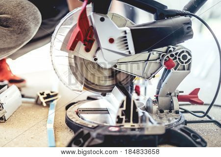 Man, Worker Using A Sliding Compound Mitre Saw With Circular Blade For Cutting Metal And Aluminium