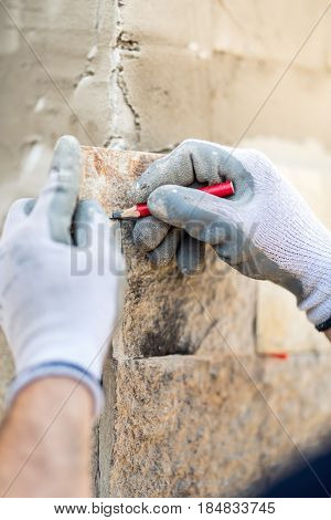Details Of Worker Hands Taking Notes And Drawing On Stone. Construction Worker Paving Home Facade Wi