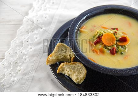 Vegetable soup with carrot red pepper and leek in a black speckled bowl on a white table cloth copy space close up selected focus very narrow depth of field