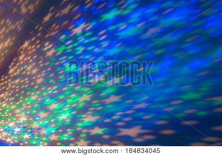 Abstraction of yellow, green, blue flickering stars