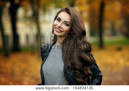 Beautiful stylish girl in gray pullover, black jeans and leather jacket standing and posing in autumn park. Pretty young woman with long curly brunette hair and red lips