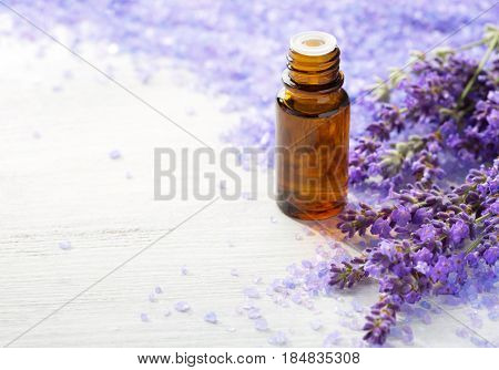 Lavender essential oil,   sprigs of lavender and  mineral bath salts on  the wooden table.  Selective focus