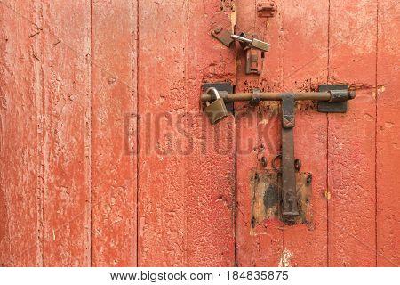 Old rusty padlock on wooden door. Home security