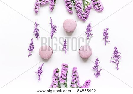 lady morning with macaroons and mauve flowers on white desk background top view