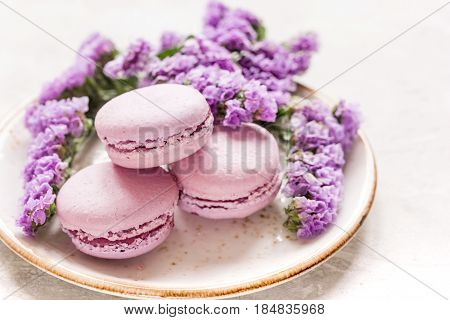 spring woman breakfast with macaroons and mauve flowers on white desk background