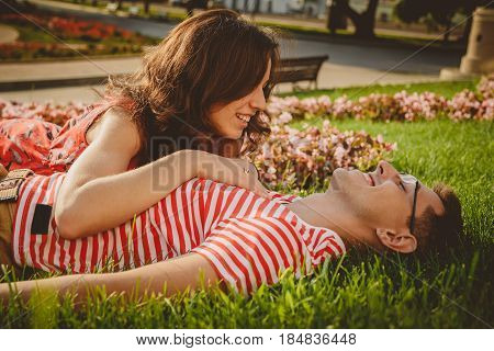 Love Story, Young Guy And Girl Lying On Green Grass, Embracing Each Other In Park And Spending Time