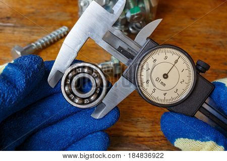 Measurement of the ball bearing outer diameter by a master in gloves with a slide caliper