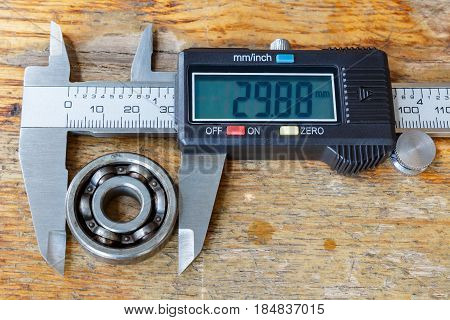 Digital caliper with ball bearing on a wooden table